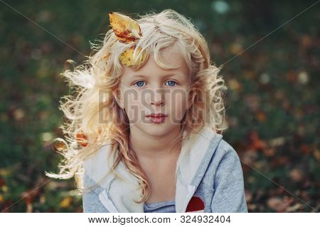 Beautiful Pretty Preschool Caucasian Blonde Girl With Autumn Leaves In Long Hair Sitting On Grass Lo