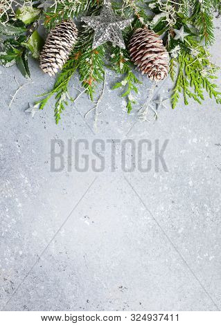 Christmas or winter background with a border of green and frosted evergreen branches and pine cones on a grey vintage board. Flat lay, winter concept with copy space.
