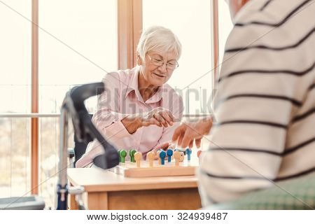Two seniors, man and woman, in a nursing home playing a board game