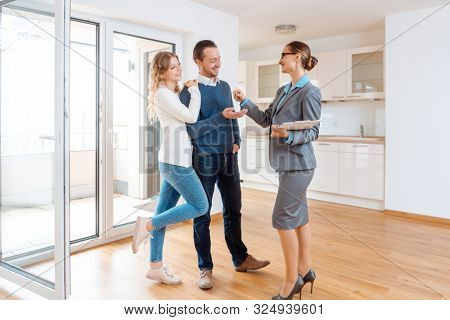Realtor giving house key to the happy buyers or tenants