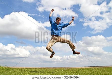 Young enthusiastic guy jumping up from the fields in the Netherlands