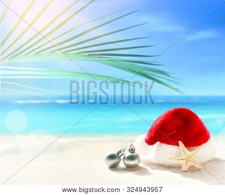 Christmas Holidays Concept. Santa Claus Hat And Christmas Ball On Summer Sand Beach. Palm Branch.
