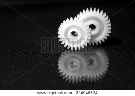 Several White Plastic Gears On A Black Mirror Background. Mechanical Repair. Fix. Reflection. Repair