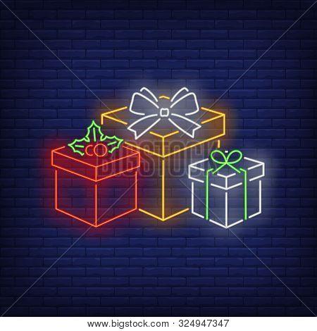 Xmas Presents Neon Sign. Pile Of Gift Boxes, Carton Wrap, Ribbon, Bow, Mistletoe. Vector Illustratio