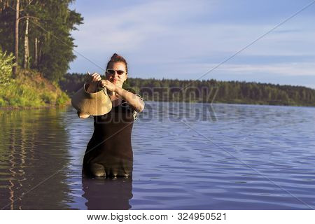A Girl In A Straw Hat She Holds In Her Hands, She Is In The Lake. A Black Dress Is Wet From The Wate