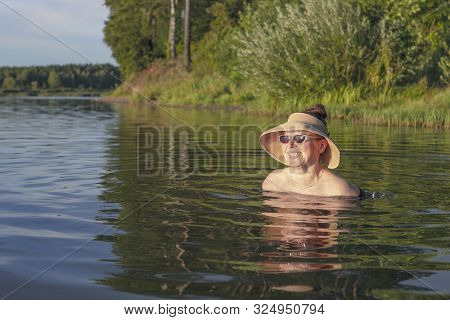 Girl In A Straw Hat, She Is In The Lake. Only The Head Is Visible Looking Into The Distance.