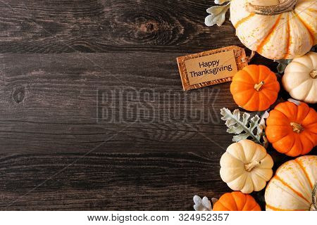 Happy Thanksgiving Tag With Fall Side Border Of Pumpkins And Leaves On A Dark Wood Background With C