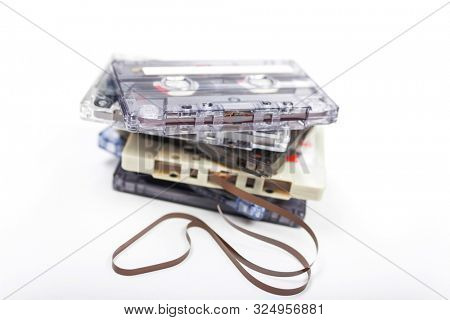 Pile of compact audio cassette tapes on a white background