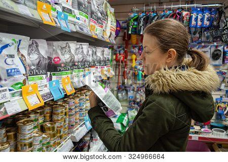 Minsk, Belarus - September 20, 2019: Man Shopping Pet Food In Pet Shop. Young Woman Reading Ingredie