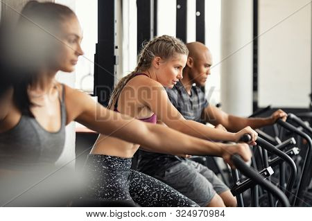 Group of determined multiethnic people at gym exercising on stationary bike. Concentrated fitness woman training on exercise bike with class. Man and women behind riding cycling machine in hard effort