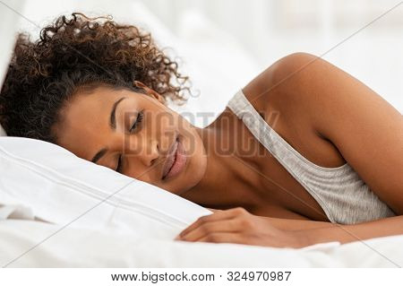 Beautiful young woman sleeping on bed in bedroom. African girl sleeping in her bed in the morning with eyes closed. Carefree black woman lying down on bed and dreaming.