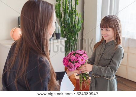Daughter Gifts Flowers And Card To Her Mother In Living Room. Child Congratulates Mom On A Holiday