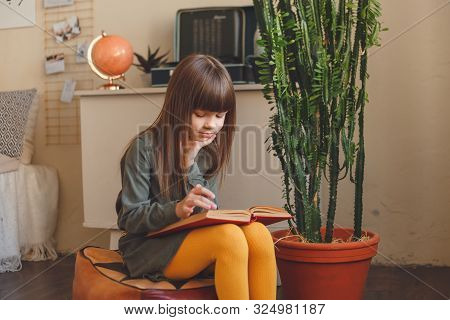 Charming Little Girl Reading Book In Her Room
