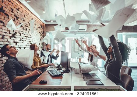Smiling Business People Having Fun By Throwing Papers In The Air Celebrating Business Success In The