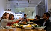 Side view of a group of young adult multi-ethnic male and female friends sitting at a table at home set for Thanksgiving dinner making a toast with glasses of red wine poster
