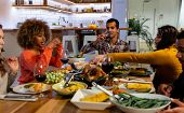 Side view of a group of young adult multi-ethnic male and female friends sitting around a table talking, drinking and serving Thanksgiving dinner at home together poster