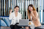 Two asian businesswomen hapiness celebrating together when checking success goal via technology laptop in modern office or coworking space, coffee break, relaxing and talking after working time poster
