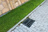 Plastic drain gutter, green grass lawn and stone pavement sidewalk. poster