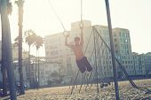 An athletic build Asian young man exercise on traveling rings early morning poster