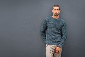 Handsome young cool man standing on grey background and looking at camera. Portrait of thoughtful casual man.Pensive stylish guy wearing sweater leaning against background with copy space.