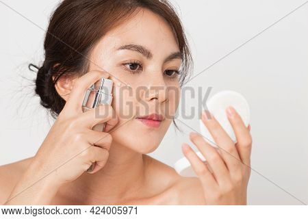 Young Asian Woman Squeezes Out Foundation Cream On Her Face. Female Applying Foundation Cream On Whi
