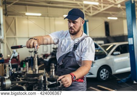 Technician Working On Checking And Service Car In Workshop Garage; Technician Repair And Maintenance