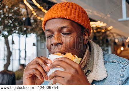 Pleasured African-america Guy In Orange Knitted Hat Eats Delicious Fresh Hamburger In Contemporary D