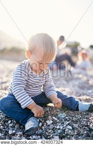 Child Sits On A Pebble Beach And Picks Up Pebbles In His Hands