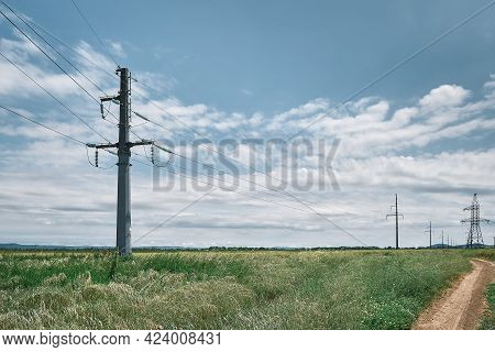 High Voltage Power Lines, Landscape On A Green Field At Noon, Bright Sunny Day, Blue Sky With Clouds