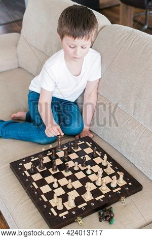 A Cute Boy Of Caucasian Appearance Plays Chess. Games For The Development Of Logic And Strategy. Che