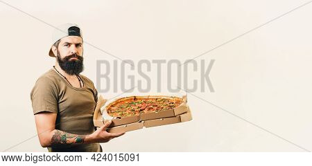 Handsome Courier Holds Cardboard Boxes With Pizza, Suggests Taste Delicious Fast Food, Wears Hat And