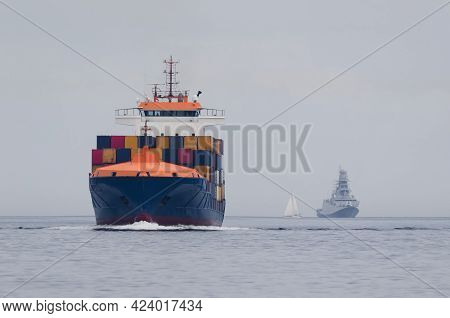 Container Ship And Warship - Freighter And Frigate Sails On The Sea