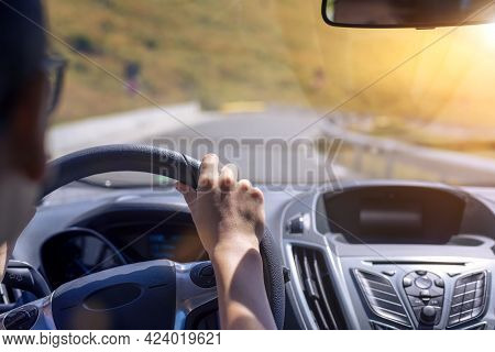 Girl Hands On The Steering Wheel Of A Car While Driving. Against The Background, The Windshield And