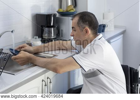 Young Man Disabled Man On Wheelchair Washing Dishes. Smiling Young Handicapped Man Sitting On Wheelc