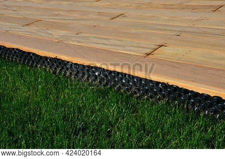 Separating The Terrace From The Lawn Using Plastic Black Foil With Knobs. Prevents Grass From Growin
