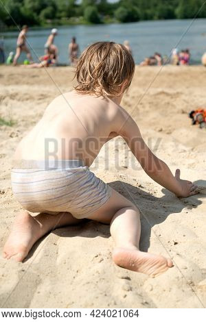 Little Boy Plays In The Sand On The Beach After Swimming On  Summer Day