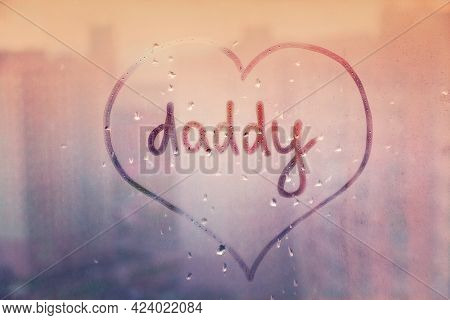 Handwritten Word Daddy In Heart Shape On Misted Sunset Pink Window With Raindrops