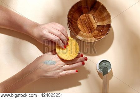 beauty, cosmetics and bodycare concept - hands with sponge applying blue cosmetic clay mask to skin on beige background