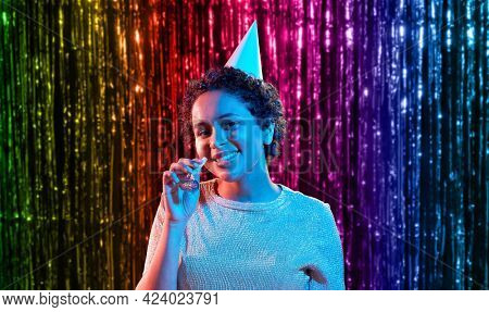 birthday, celebration and lgbt concept - happy smiling young african american woman in party cap with blower in ultraviolet neon lights over foil fringe curtain in rainbow colors background