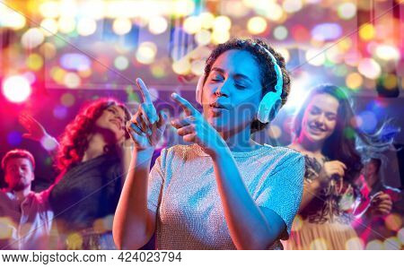 nightlife, technology and people concept - happy young african american woman in headphones listening to music and dancing in neon lights over nightclub background