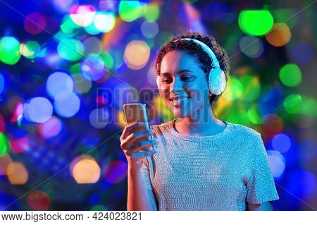 nightlife, fashion and people concept - happy young african american woman with smartphone and headphones in neon lights over bokeh background