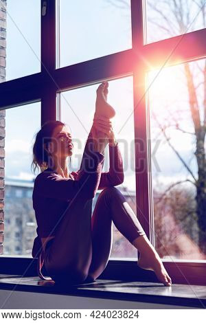 fitness, sport and healthy lifestyle concept - woman doing yoga exercise on window sill at studio over sunlight