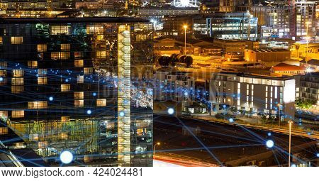 Glowing blue network of connections against view of cityscape at night. global networking and connection technology concept