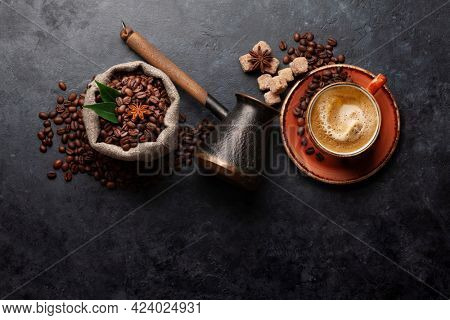Roasted coffee beans, Turkish jezve, espresso coffee cup and brown sugar. Top view flat lay with copy space