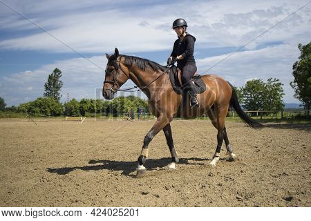 The Girl With Helmet Riding A Horse At A Riding School