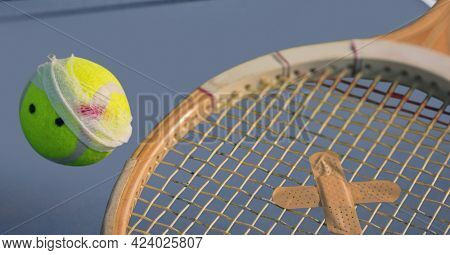 Composition of tennis ball and racket with plaster on tennis court. injury, sports and competition concept digitally generated image.