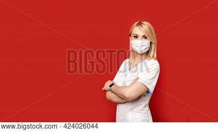 Confident Female Doctor Wearing Protective Face Mask Standing On Red Background Arms Crossed. Young