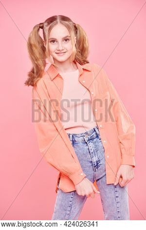 Teenage style. Pretty teenage girl in bright summer clothes and with funny ponytails smiling at camera.