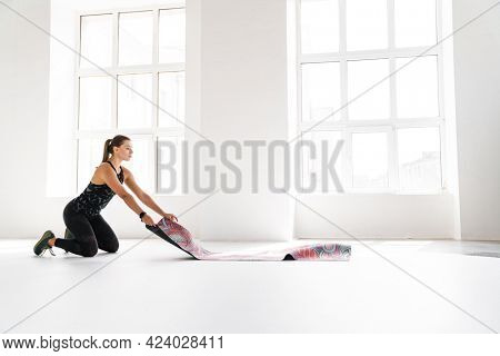 Young white woman unrolling fitness mat before practice indoors