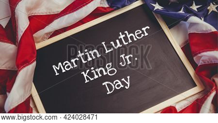 Martin luther day text on wooden slate against american flag. martin luther day template background design concept